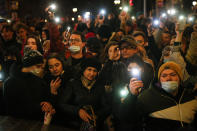 People shine the lights of their mobile phones during the opposition rally in support of jailed opposition leader Alexei Navalny in Moscow, Russia, Wednesday, April 21, 2021. Police across Russia have arrested more than 180 people in connection with demonstrations in support of imprisoned opposition leader Alexei Navalny, according to a human rights group. (AP Photo/Alexander Zemlianichenko)
