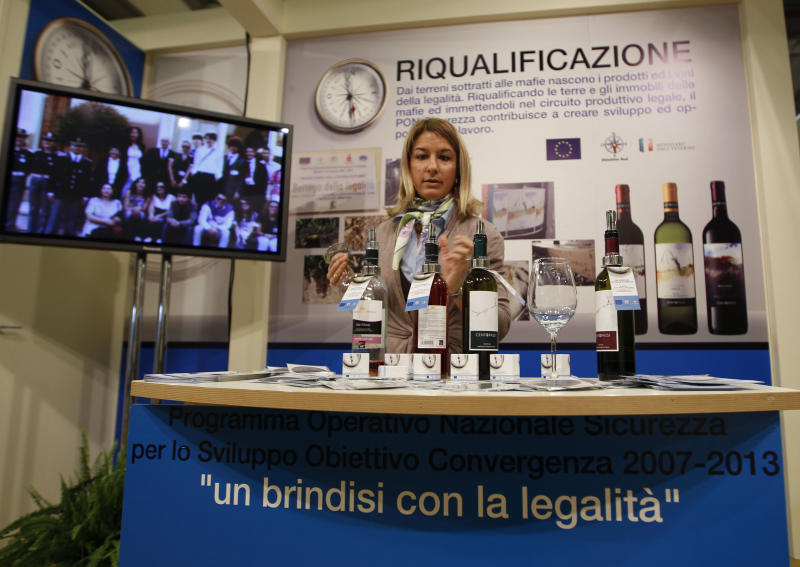 "A woman prepares bottles of wine in a 'Pon sicurezza project' stand at the 46th edition of the annual International Wine and Spirits Exhibition ""Vinitaly"", in Verona, northern Italy, Monday, March 26, 2012. The prize-winning Sicilian white wine Grillo is blended from native grape varieties grown at an altitude of 600 meters (1,900-feet.) But there's an additional appeal that escapes the palate: the vineyard have been cultivated on lands once held by the Mafia. (AP Photo/Luca Bruno)"