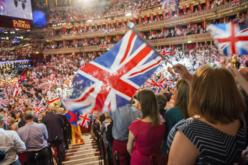 "FILE  - In this Sept. 13, 2014 file photo, members of the audience react during the Last Night of the Proms at the Royal Albert Hall, London. The BBC has ditched the lyrics of ""Rule Britannia!"" for its traditional summer-ending concert amid a controversy over the song's celebration of the British Empire at a time when critics are re-evaluating the nation's colonial past. Britain's publicly funded broadcaster said the final night of its Proms concert series would feature instrumental versions of ""Rule Britannia!"" and ""Land of Hope and Glory,"" instead of traditional singalongs.  (Guy Bell/PA via AP, File)"