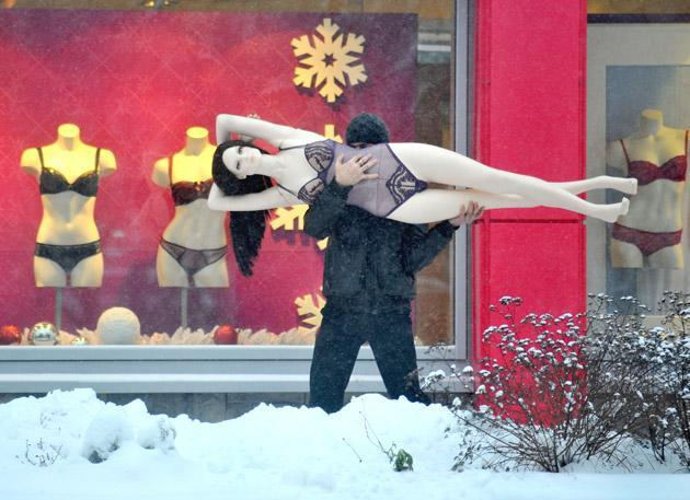 A man carries a mannequin in the Belarus capital Minsk, on December 10, 2012. AFP PHOTO / VIKTOR DRACHEV