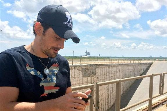 """Country music star Brad Paisley uses his phone to 'leak' his new song, """"American Flag on the Moon"""" from NASA's historic Launch Pad 39B at the Kennedy Space Center in Florida."""