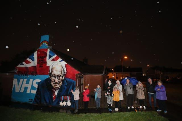Local residents stand beside a mural of Captain Sir Tom Moore in Clonduff, east Belfast