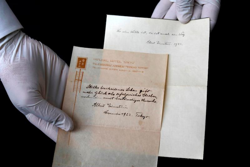 Gal Wiener, owner and manager of the Winner's auction house in Jerusalem, displays two notes written by Albert Einstein