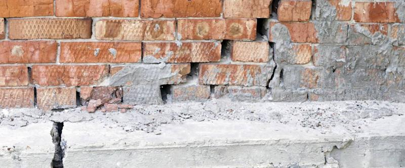 Large crack in a reinforced concrete foundation and brick wall