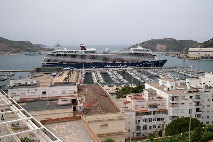 This image shows the tops of buildings in front of a cruise ship docked in Spain.