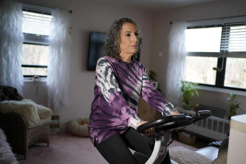 Catherine Busa rides an exercise bike as part of her recovery from COVID-19 at her home in New York, Wednesday, Jan. 13, 2021. The 54-year-old New York City school secretary didn't have any underlying health problems when she caught the coronavirus in March and recovered at her Queens home. But some symptoms lingered. After eights months of suffering, she made her way to Jamaica Hospital Medical Center — to a clinic specifically for post-COVID-19 care. (AP Photo/Seth Wenig)