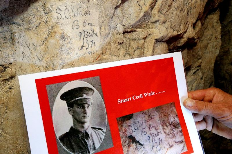 "A portrait of Stuart Cecil Wade (June 1916) shown near his name etched in the stone on April 21, 2016 in the ""underground city"" of Naours, France (AFP Photo/Francois Nascimbeni)"