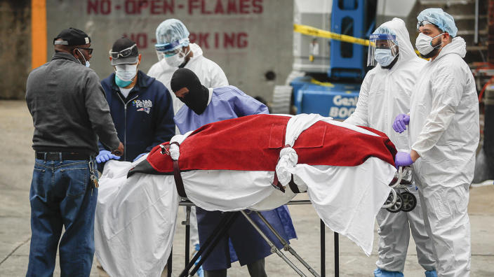 A body wrapped in plastic that was unloaded from a refrigerated truck is handled by medical workers wearing personal protective equipment due to COVID-19 concerns at Brooklyn Hospital Center. (AP Photo/John Minchillo)