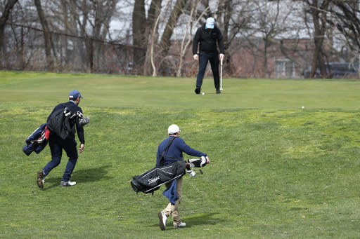 Two golfers approach the green as another golfer finishes his hole at Forest Park Golf Course, Friday, March 20, 2020, in New York. Its not hard for golfers to keep their distance on the fairway, but greens and especially tee boxes can become more crowded and golf is popular among age groups most vulnerable to the virus. (AP Photo/Kathy Willens)