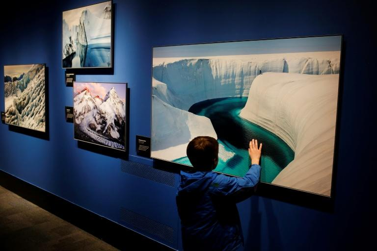 "A boy touches one of the photos displayed at the ""Extreme Ice"" exhibit by US photographer James Balog at the Museum of Science and Industry in Chicago, Illinois"