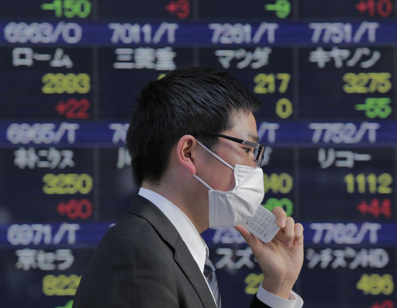 A man walks by the electronic stock board of a securities firm in Tokyo, Tuesday, Jan. 22, 2013. Asian stock markets wavered between gains and losses Tuesday after Japan's central bank ceded to political pressure and announced stimulus measures aimed at extricating the country from years of economic malaise. (AP Photo/Itsuo Inouye)