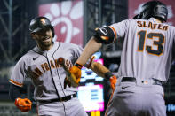 San Francisco Giants' Curt Casali, left, celebrates his home run against the Arizona Diamondbacks with Austin Slater (13) during the fifth inning of a baseball game Tuesday, Aug. 3, 2021, in Phoenix. (AP Photo/Ross D. Franklin)