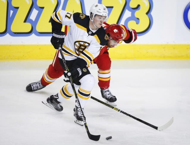 Boston Bruins' Ryan Donato, left, steals the puck away from Calgary Flames' James Neal during an NHL hockey game in Calgary, Alberta, Wednesday, Oct. 17, 2018. (Jeff McIntosh/The Canadian Press via AP)
