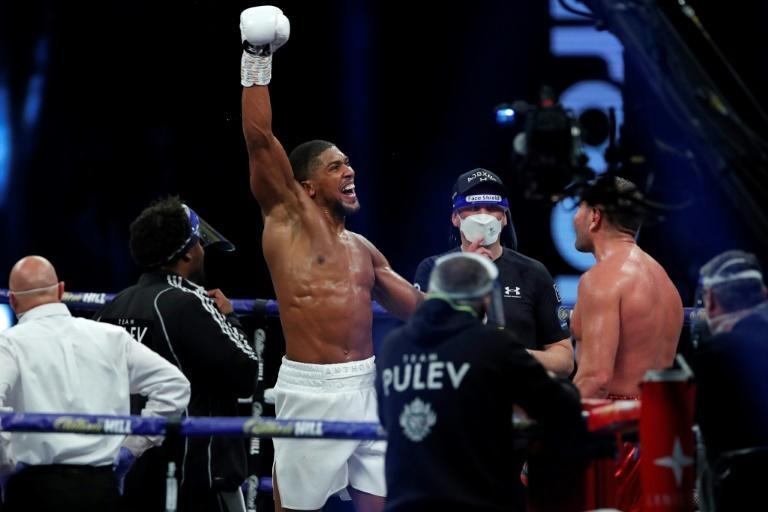 Need to fight Fury: Britain's Anthony Joshua (L) pictured celebrating after his world heavyweight title win over Bulgaria's Kubrat Pulve at Wembley in December 2020 (AFP/ANDREW COULDRIDGE)