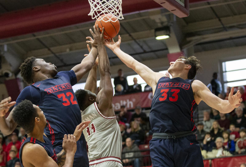 Dayton center Jordy Tshimanga (32) and forward Ryan Mikesell (33) reach for a rebound with Saint Joseph's guard Toliver Freeman (11) during the first half of an NCAA college basketball game, Sunday, Jan. 5, 2020, in Philadelphia. (AP Photo/Laurence Kesterson)