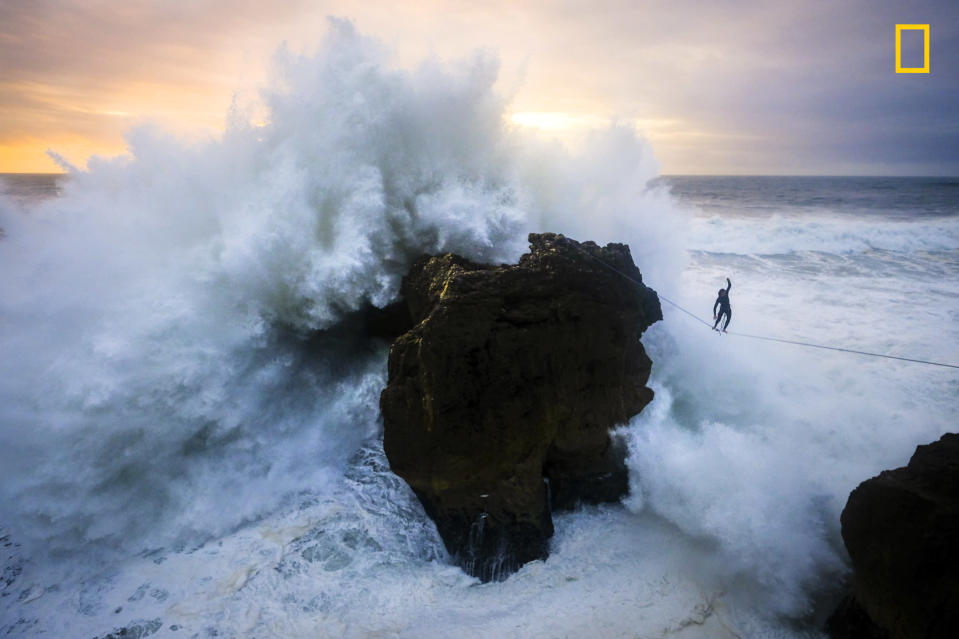 <p>Andrey Karr from Western Riders Slacklines at sunset above big waves in Nazare, Portugal, Dec. 27, 2017. (© Aidan Williams/National Geographic Travel Photographer of the Year Contest) </p>