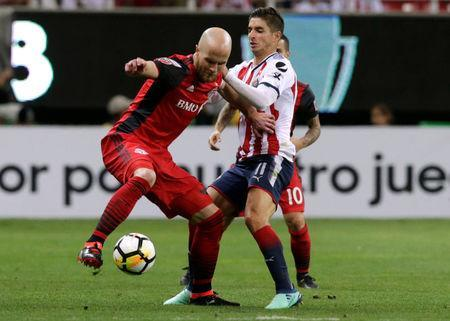 Soccer Football - CONCACAF Champions League Final Second Leg - Guadalajara vs Toronto FC - Estadio Akron, Guadalajara, Mexico - April 25, 2018 Guadalajara's Isaac Brizuela in action with Toronto's Michael Bradley REUTERS/Henry Romero