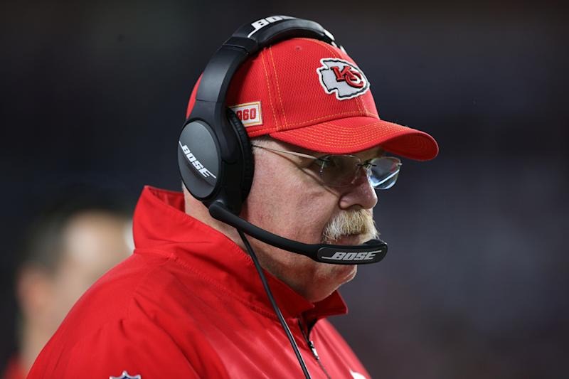 Andy Reid looks on during the Super Bowl while wearing a headset and red Chiefs hat.