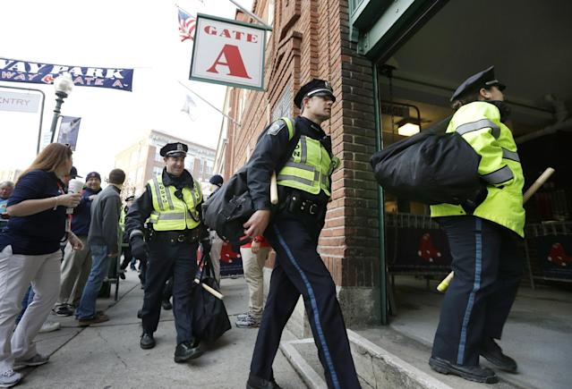 Boston police carry bags and batons as they enter Fenway Park before Game 6 of baseball's World Series between the Boston Red Sox and the St. Louis Cardinals, Wednesday, Oct. 30, 2013, in Boston. (AP Photo/Steven Senne)