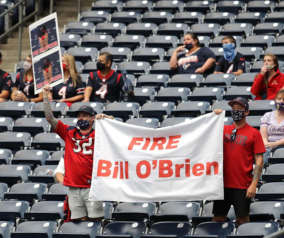 "Texans fans hold up a ""Fire Bill O'Brien"" banner while wearing masks."
