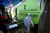 A health worker walks past a mobile testing van meant for taking samples to test for COVID-19 in New Delhi, India, Saturday, Dec. 19, 2020. India's confirmed coronavirus cases have crossed 10 million with new infections dipping to their lowest levels in three months, as the country prepares for a massive COVID-19 vaccination in the new year. (AP Photo/Manish Swarup)
