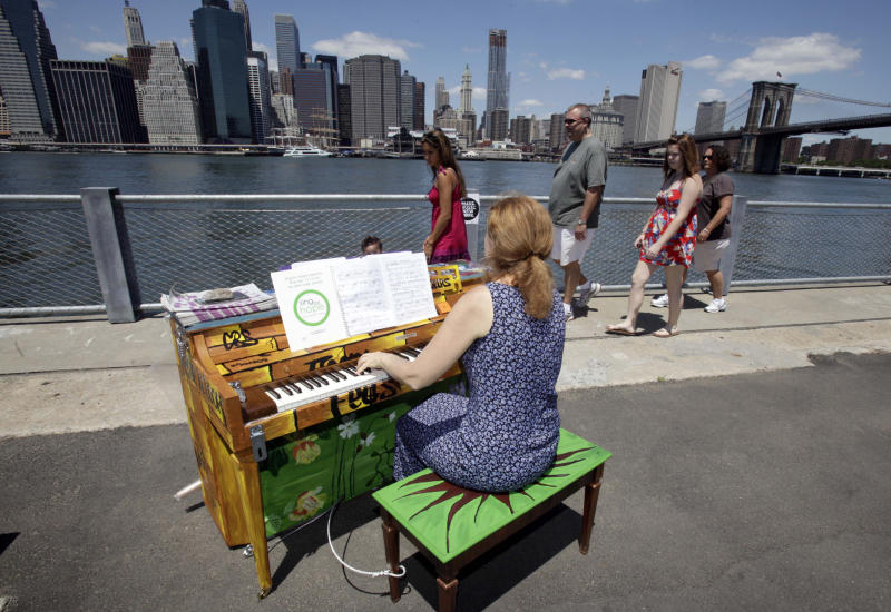 FILE - In this June 21, 2010 file photo, Carolyn Enger, of Englewood, N.J., plays a piano in Brooklyn Bridge Park, in the Brooklyn borough of New York. The piano was one of 60 that were part of the first year of Sing for Hope's Pianos, a grassroots group of more than 1,000 artists who volunteer to make art accessible to everyone. (AP Photo/Richard Drew, File)