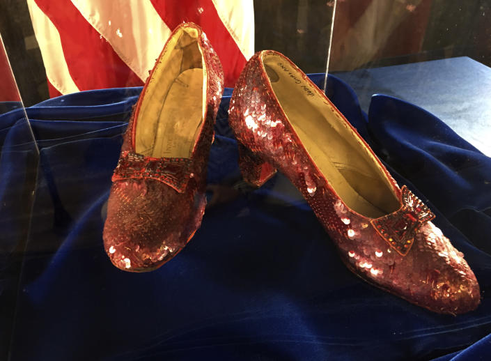 """A pair of ruby slippers once worn by actress Judy Garland in the """"The Wizard of Oz"""" are displayed at a news conference Tuesday, Sept. 4, 2018, at the FBI office in Brooklyn Center, Minn. Authorities announced that the slippers, stolen in 2005 from the Judy Garland Museum in Grand Rapids, Minn., were recovered in a sting operation. The FBI says it has multiple suspects in the extortion and that the investigation continues. Four pairs of ruby slippers worn by Garland in the movie are known to exist. Judy Garland's name can be seen in the shoe at right. (AP Photo/Jeff Baenen)"""