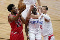 Chicago Bulls forward Thaddeus Young, left, drives to the basket against Los Angeles Clippers guard Reggie Jackson, center, and center Ivica Zubac during the first half of an NBA basketball game in Chicago, Friday, Feb. 12, 2021. (AP Photo/Nam Y. Huh)