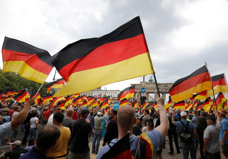 "Alternative for Germany (AfD)'s demonstrators wave German flags in front of the Brandenburg Gate (Brandenburger Tor) in Berlin during the ""demonstration for the future of Germany"" called by the far-right AfD in Berlin on May 27, 2018. Photo: ODD ANDERSEN/AFP/Getty Images"