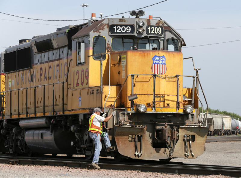 FILE - In this July 20, 2017, file photo, a Union Pacific employee climbs on board a locomotive in a rail yard in Council Bluffs, Iowa. This year's scheduled completion of a $15 billion automatic railroad braking system will bolster the industry's argument for eliminating one of the two crew members in most locomotives. But labor groups argue that single-person crews would make trains more accident prone. (AP Photo/Nati Harnik, File)