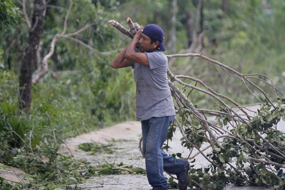 A worker cleans fallen branches after Hurricane Zeta passed through Playa del Carmen, Mexico, early Tuesday, Oct. 27, 2020. Zeta is leaving Mexico's Yucatan Peninsula on a path that could hit New Orleans Wednesday night. (AP Photo/Tomas Stargardter)
