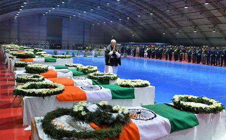 India's Prime Minister Narendra Modi pays tribute as he walks next to the coffins containing the remains of Central Reserve Police Force (CRPF) personnel who were killed after a suicide bomber rammed a car into a bus carrying them in south Kashmir on Thursday, at Palam airport in New Delhi, India, February 15, 2019. India's Press Information Bureau/Handout via REUTERS