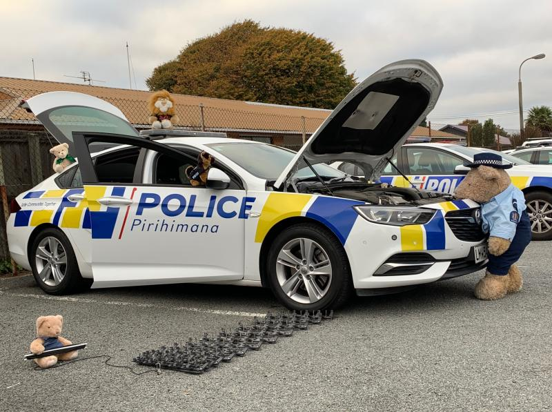 A number of stuffed bears are pictured with a New Zealand Police car in Christchurch.
