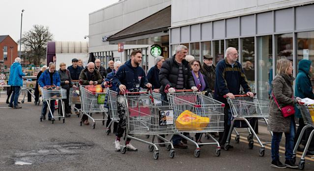 People queue to shop at Sainsbury's supermarket in Leamington Spa, Warwickshire, where the store had announced that the first hour of opening would be for elderly and vulnerable customers. (PA)