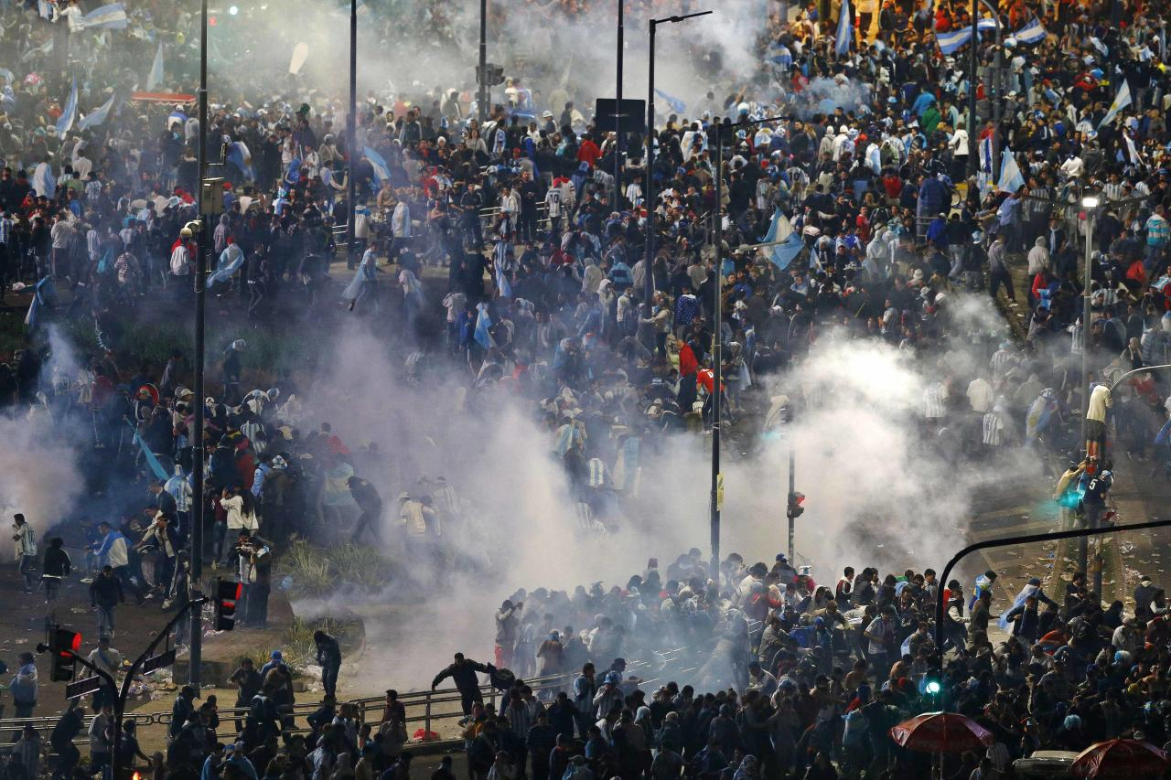 Argentina's fans run away from tear gas as they clash with riot police in Buenos Aires after Argentina lost to Germany in their 2014 World Cup final soccer match in Brazil, July 13, 2014. REUTERS/Ivan Alvarado (ARGENTINA - Tags: CIVIL UNREST SPORT SOCCER WORLD CUP)