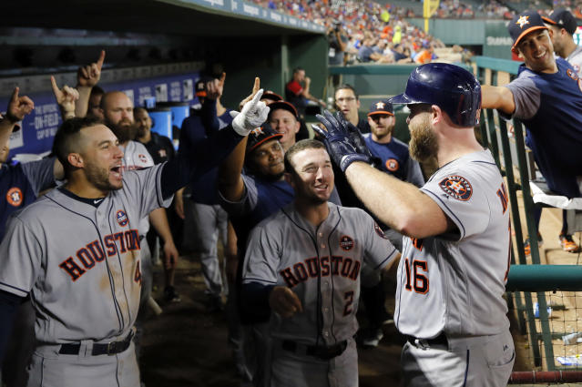 Houston Astros' George Springer (4), Alex Bregman (2) and the rest of the dugout celebrate after Brian McCann hit a two-run home run in the fifth inning against the Texas Rangers. (AP)