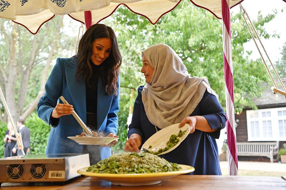 <p>Meghan helps to prepare food at an event at Kensington Palace to mark the launch of a cookbook with recipes from a group of women affected by the Grenfell Tower fire.</p>
