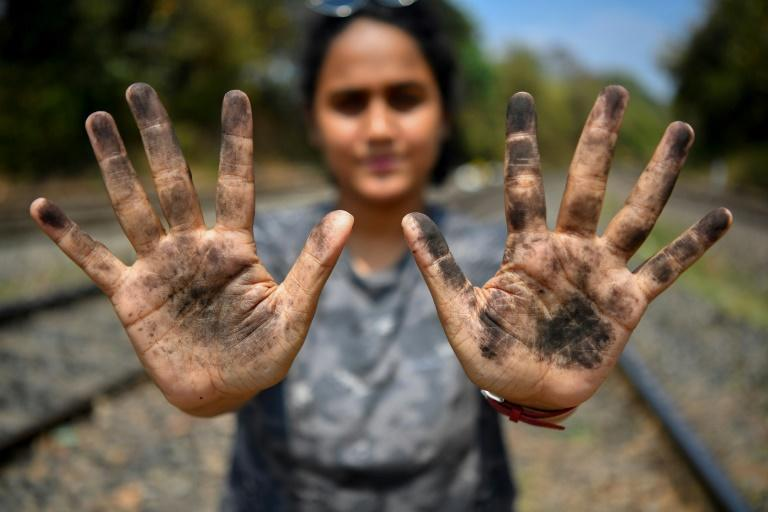 Zoologist Hycintha Aguiar shows her soot-covered hands after handling coal fallen onto railway tracks from a cargo train at the Kulem railway station in Goa