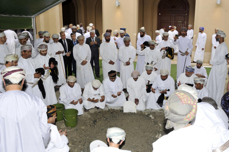 In this photo made available by Oman News Agency, Omani officials pray over the grave of Sultan Qaboos after his burial in Muscat, Oman, Saturday, Jan. 11, 2020. Sultan Qaboos bin Said, the Mideast's longest-ruling monarch who seized power in a 1970 palace coup and pulled his Arabian sultanate into modernity while carefully balancing diplomatic ties between adversaries Iran and the U.S., has died. He was 79. (Oman News Agency via AP)