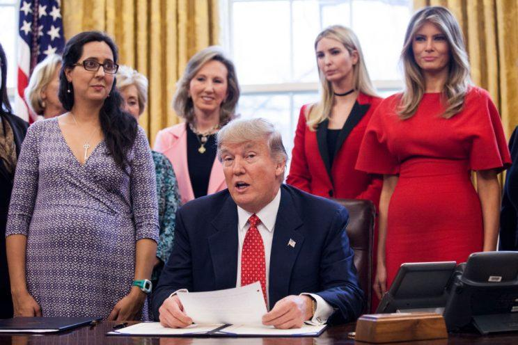 Trump holds papers at his desk with red-dress-wearing Melania, among others, standing behind him.