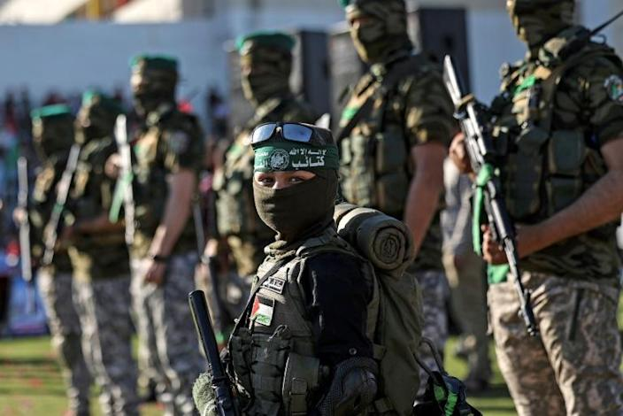 A Palestinian boy carries a toy gun while standing with members of Al-Qassam Brigades, the armed wing of the Hamas movement, during a rally in Gaza City on May 24