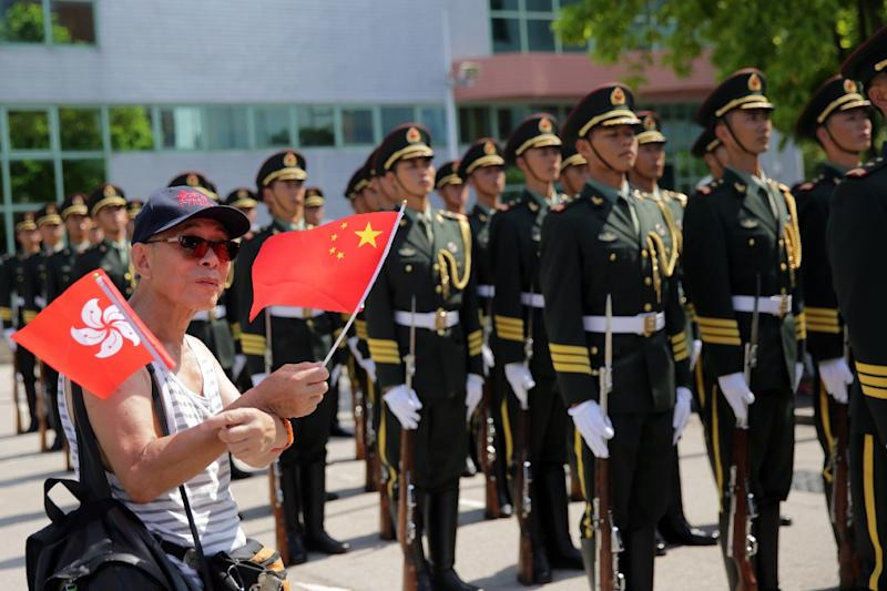 A member of the public waves the Chinese and Hong Kong flags as Peoples' Liberation Army (PLA) soldiers stand in the background at the Ngong Shuen Chau Barracks in Hong Kong on July 1, 2015