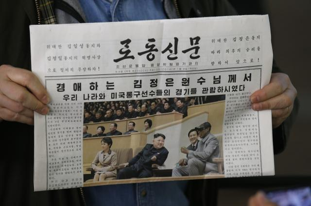 U.S. tourist Sokmensuer shows copy of North Korea's Rodong Sinmun newspaper featuring North Korean leader Kim and Rodman, in Beijing airport