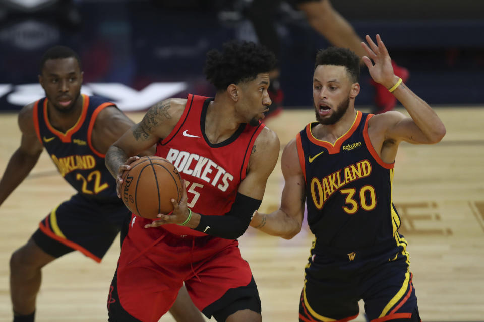 Houston Rockets' Christian Wood, left, against Golden State Warriors' Stephen Curry during the first half of an NBA basketball game in San Francisco, Saturday, April 10, 2021. (AP Photo/Jed Jacobsohn)