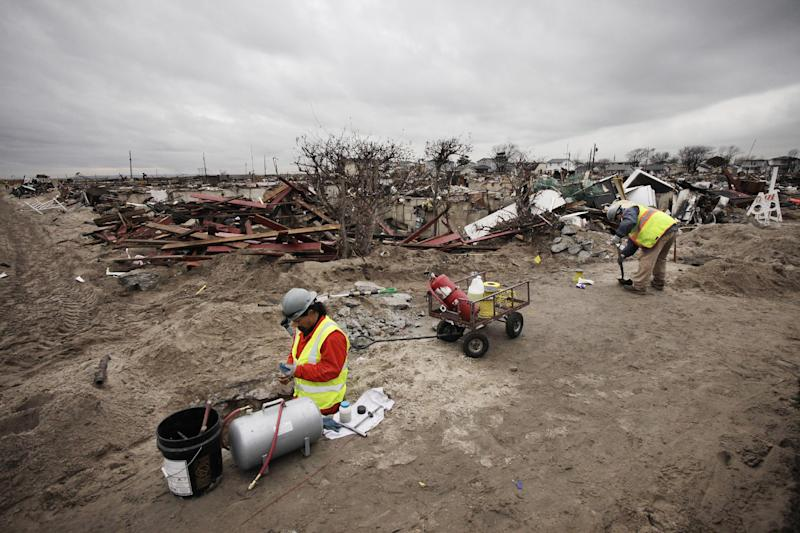 Frank Tatulli, left, stands in a shallow pit as he installs a natural gas line in the fire-damaged zone in the Breezy Point section of New York, Friday, Dec. 7, 2012. Over 100 homes were burned to the ground during Superstorm Sandy. (AP Photo/Mark Lennihan)