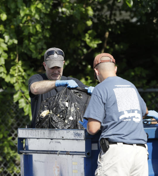 Investigators take out a black trash bag from a dumpster Sunday, July 21, 2013 near where three bodies were recently found in East Cleveland, Ohio. Searchers rummaging through vacant houses in a neighborhood where three female bodies were found wrapped in plastic bags should be prepared to find one or two more victims, a police chief said Sunday. (AP Photo/Tony Dejak)