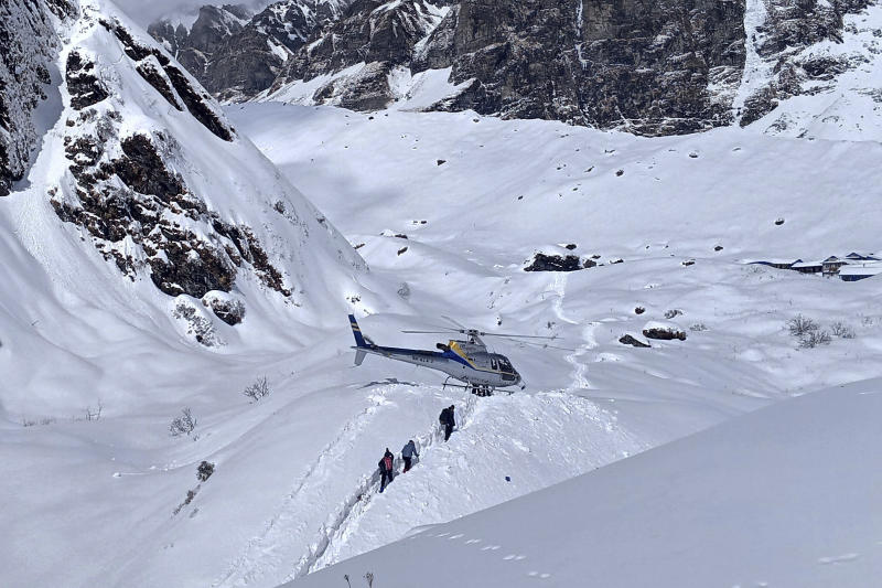 In this Saturday, Jan. 18, 2020 photo, trekkers are being rescued in a helicopter a day after an avalanche hit Mount Annapurna trail in Nepal. Special army and government rescue personnel were searching again on Monday for four South Korean trekkers and their three Nepali guides lost since an avalanche swept a popular trekking route in Nepal's mountains. (AP Photo/Phurba Ongel Sherpa)