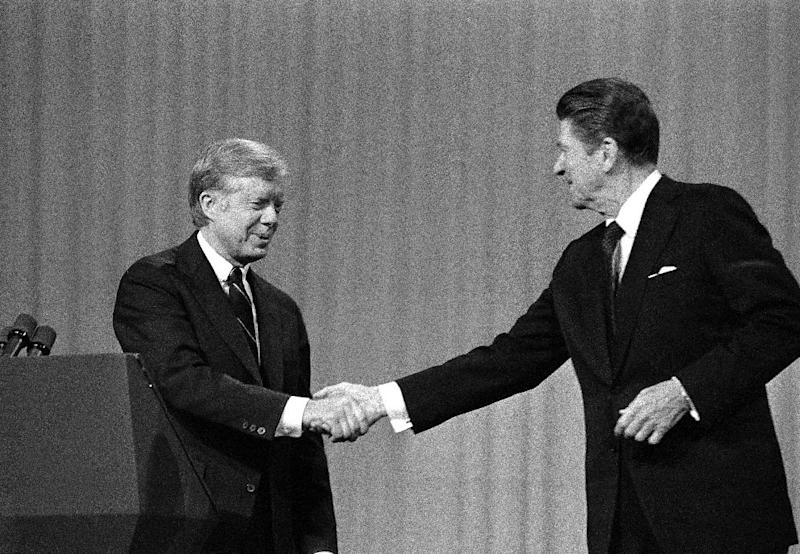 """FILE - This Oct. 28, 1980 black-and-white file photo shows President Jimmy Carter, left, and Republican Presidential candidate Ronald Reagan shake hands after debating in the Cleveland Music Hall in Cleveland. In presidential politics, everybody's searching for """"the moment."""" The campaigns don't know when or how it will come, but they watch for something _ awkward words or an embarrassing image _ that can break through and become the defining symbol of the other guy's flaws. Now all eyes are on the series of three presidential debates that starts Wednesday. (AP Photo/Madeline Drexler, File)"""