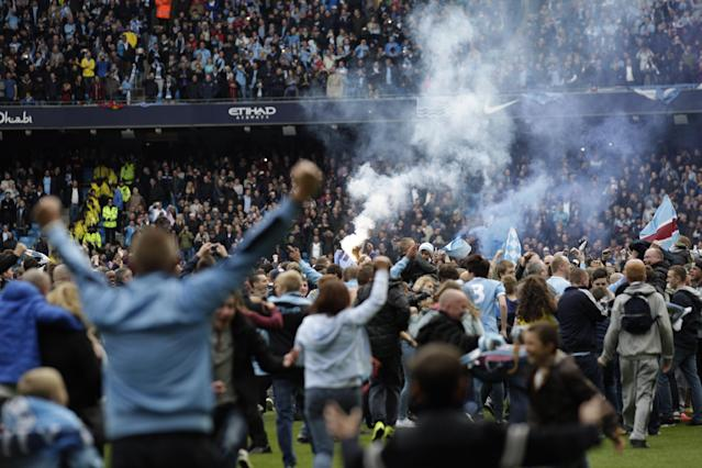 A flare is held up as Manchester City fans invade the pitch at the end of the English Premier League soccer match between Manchester City and West Ham at the Etihad Stadium in Manchester, England, Sunday May 11, 2014. Manchester City won the Premier League for the second time in three seasons on Sunday, completing its campaign with a comfortable 2-0 victory over West Ham that lacked any of the drama of its previous title. (AP Photo/Jon Super)