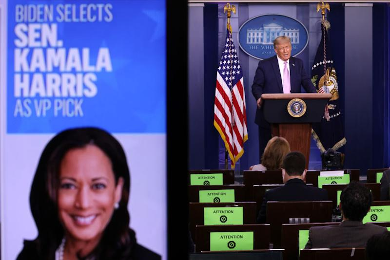 President Donald Trump speaks as a picture of Kamala Harris is seen on a screen during a news conference this morning. Source: Getty